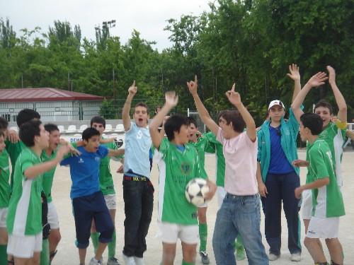 Todo el equipo celebrando la victoria con los aficionados en el centro del campo