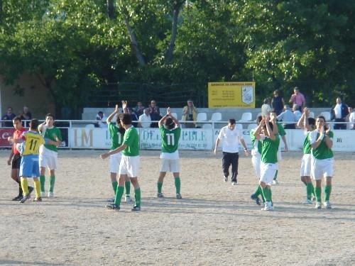 Los dos equipos dandose la mano deportivamente en el centro del campo