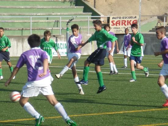 Santiago Rey despejando un balón en el centro del campo.